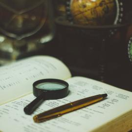 Image of book with magnifying glass